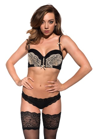 undergarment: Beautiful young brunette in black and gold lingerie