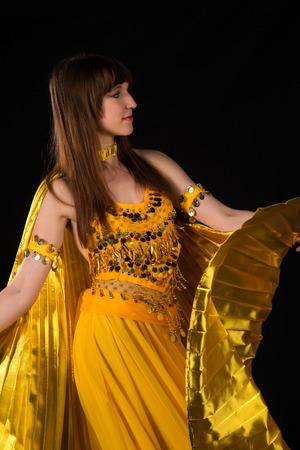 dance costume: Tall slim brunette in a yellow belly dance costume Stock Photo