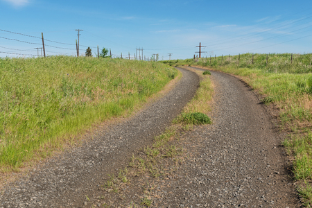 Dirt road and barbed wire fence on a hill, Colfax, Washington