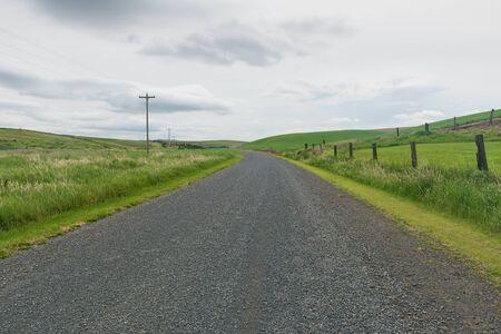 unpaved road: Gravel road through wheat fields, Palouse, Washington Stock Photo