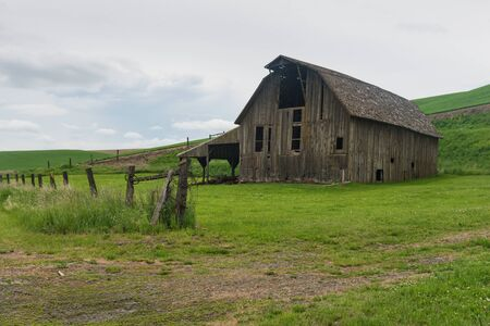 farm structures: Old barn and barbed wire fence, Palouse, Washington Stock Photo