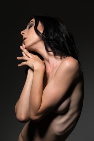 ragazza nuda: Piuttosto giovane bruna snella in piedi nudo sul grigio Archivio Fotografico