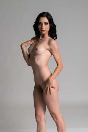 Pretty young slender brunette standing nude on gray Stock Photo