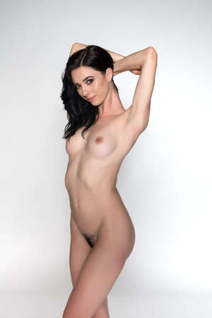 Pretty young slender brunette standing nude on white Stock Photo