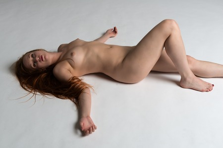 nudity young: Pretty young redhead nude on gray Stock Photo