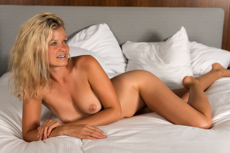 Beautiful statuesque blonde woman nude in bed
