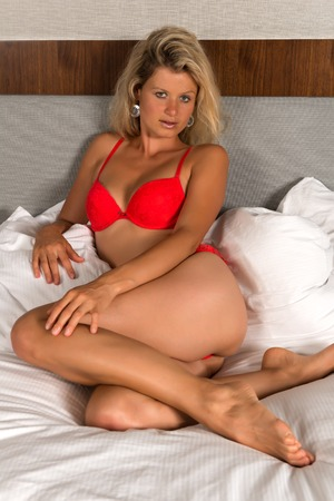 undergarment: Beautiful statuesque blonde woman in bright red lingerie
