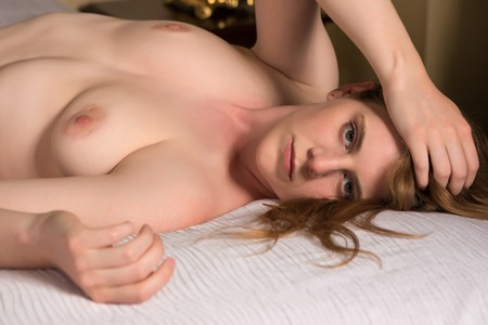 Pretty statuesque blonde lying in bed Stock Photo