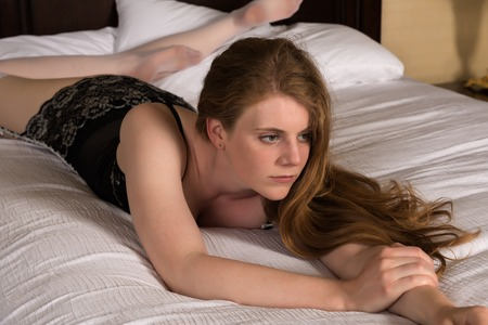statuesque: Pretty statuesque blonde lying in bed Stock Photo