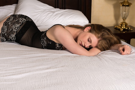 garters: Pretty statuesque blonde lying in bed Stock Photo