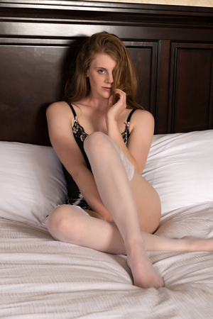 statuesque: Pretty statuesque blonde sitting in bed Stock Photo