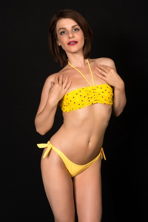 bikini slender: Pretty petite brunette in a yellow bandeau bikini Stock Photo