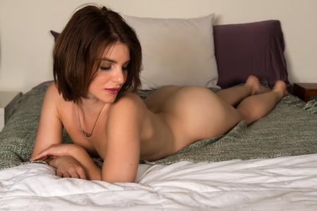 nude woman: Bastante peque�a morena desnuda acostada en la cama