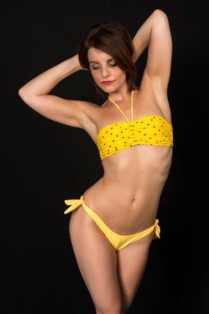 bandeau: Pretty petite brunette in a yellow bandeau bikini Stock Photo