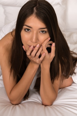 undressed woman: Beautiful petite Eurasian woman wrapped in a bedsheet