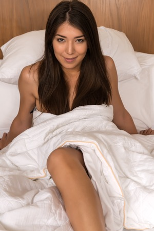 topless brunette: Beautiful petite Eurasian woman wrapped in a bedsheet