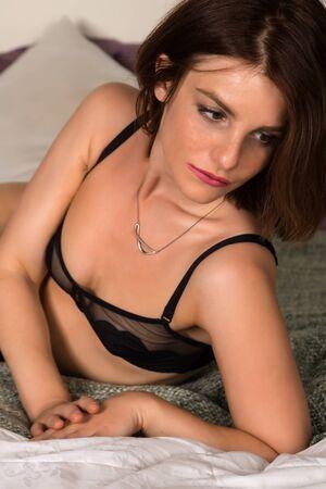 woman bra: Pretty petite brunette in bed in black lingerie
