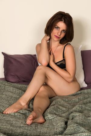 femme en sous vetements: Jolie petite brune au lit en lingerie noire