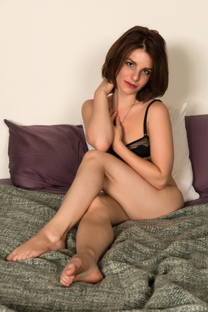 Pretty petite brunette in bed in black lingerie