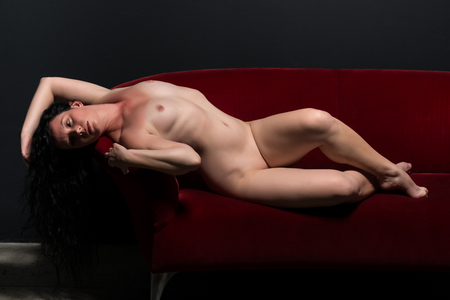 Petite pretty nude Italian brunette on a red satin couch Stock Photo