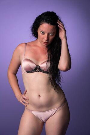 sunburnt: Petite pretty Italian brunette in pink lingerie Stock Photo