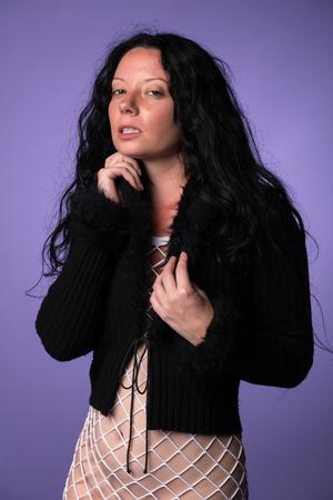 fishnet: Petite Italian brunette in a fuzzy black sweater and white fishnet dress Stock Photo