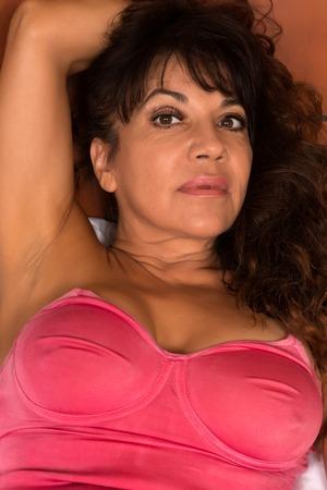 brown skin: Pretty mature brunette in a rose bodysuit Stock Photo