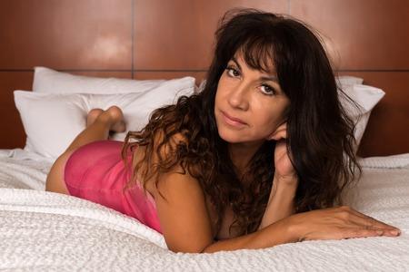 mature brunette: Pretty mature brunette in a rose bodysuit Stock Photo