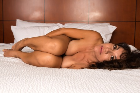 sexy topless women: Pretty mature brunette lying nude in bed Stock Photo