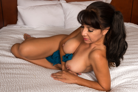 nudity: Pretty mature brunette lying nude in bed Stock Photo