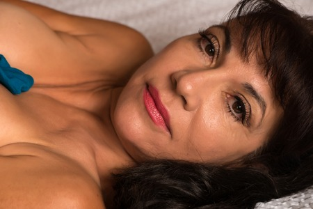 mature brunette: Closeup on the face of a pretty mature brunette in bed