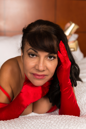 brown skin: Pretty mature brunette in bright red lingerie and opera gloves Stock Photo