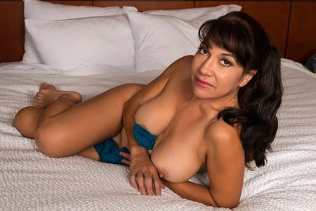 femme se deshabille: Jolie brune mature couch�e nue dans son lit