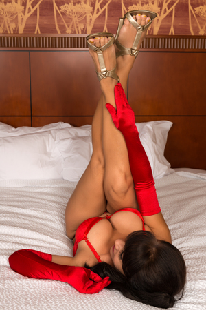undergarment: Pretty mature brunette in bright red lingerie and opera gloves Stock Photo