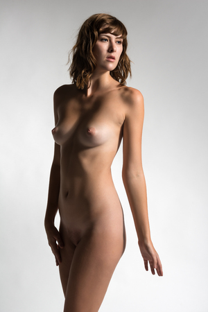 Beautiful tall brunette standing nude on gray