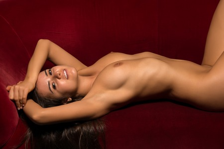 sexy topless women: Pretty Romanian brunette lying nude on a red couch