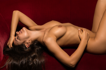 nudity young: Pretty Romanian brunette lying nude on a red couch