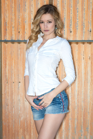 white blouse: Pretty slender blonde woman in a white blouse and denim shorts