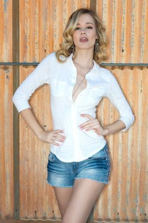 denim shorts: Pretty slender blonde woman in a white blouse and denim shorts