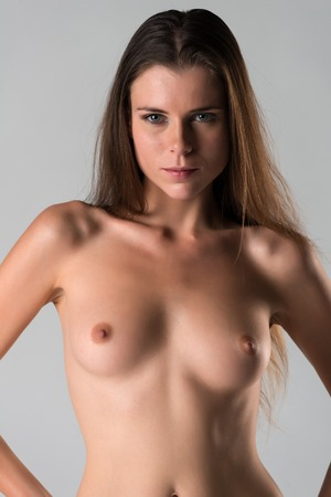 Beautiful slender young brunette nude on gray