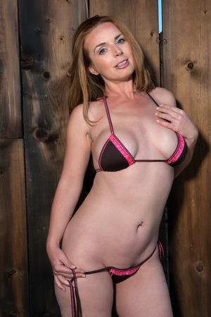 Beautiful tall redhead in a pink and brown bikini