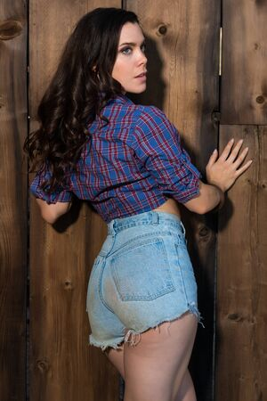 bluejeans: Pretty young brunette in a purple blouse and denim shorts Stock Photo
