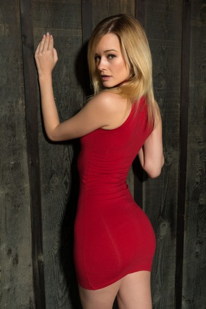 Pretty slender blonde woman in a short red dress