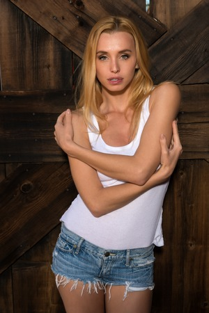 bluejeans: Beautiful slender Czech blonde in a white tank top and denim shorts Stock Photo