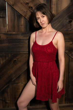 Statuesque young brunette in a short red dress Stock Photo