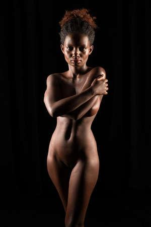 Petite Rwandan woman standing nude on black