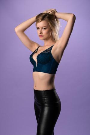 leggings: Pretty slender blonde woman in a teal bodice and black leggings