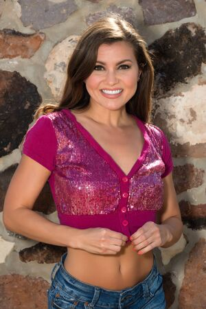 sequined: Pretty petite brunette in a purple sequined blouse and denim shorts Stock Photo