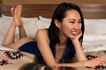 Pretty slender Chinese woman nude under a blue blouse Stockfoto