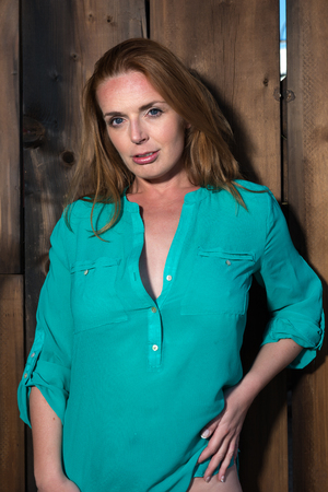 Beautiful tall redhead in a teal blouse